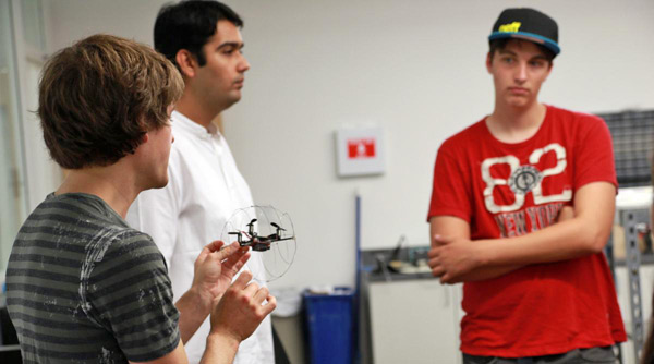 Graduate student Chris Pratt shows visitors a small aerial terrestrial robot.
