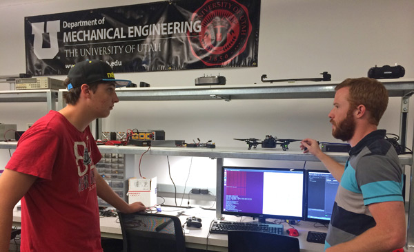 Graduate student Daman Bareiss (right) talks about research in aerial robots and collision avoidance.